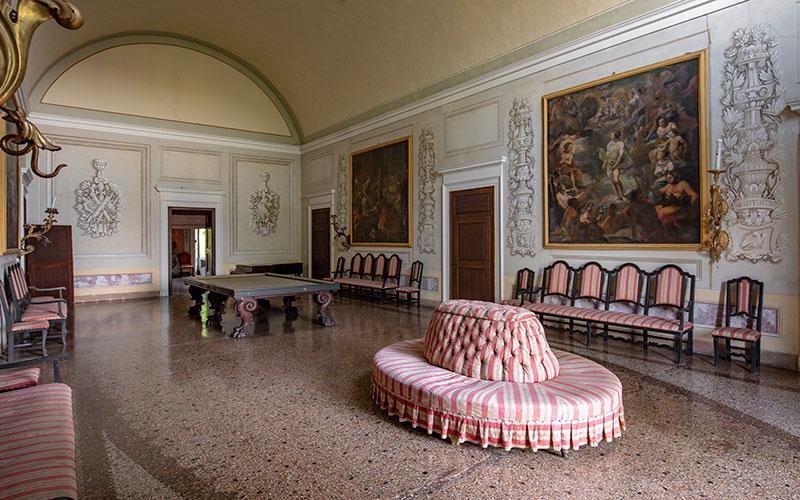Villa Malaspina interno. Sala del biliardo con sedie e divano circolare.