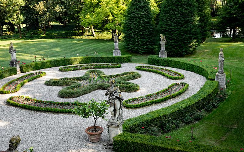Giardino all'inglese di Villa Malaspina particolare con aiuola e statue a semicerchio.